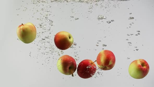 Cover Image for Colorful Apples Red and Yellow Falling Into Water with Splashes and Drops on Clean White Background