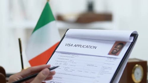 Manager Looking Through Italian Visa Application, Marking Approved, Permission