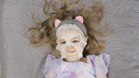 Teen Girl Applying Moisturizing Face Mask. Child Kid Take Care of Skin with Cosmetic Facial Mask