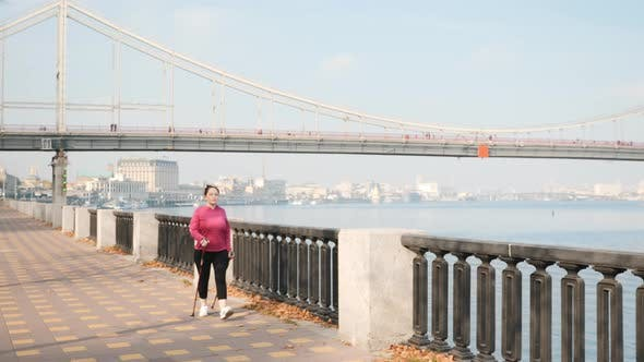 Thumbnail for Nordic walking concept. Cute female training in city promenade with bridge on background