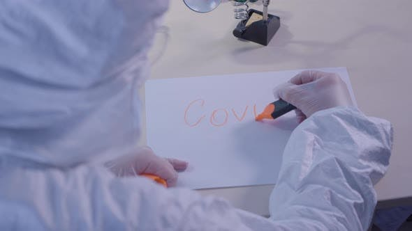 Health Care Worker in Protective Antiviral Suit Writing Covid-19 on a Sheet of Paper