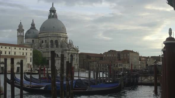 Thumbnail for Docked Gondolas Rocking Among Poles, Historical Cathedral Facing Channel
