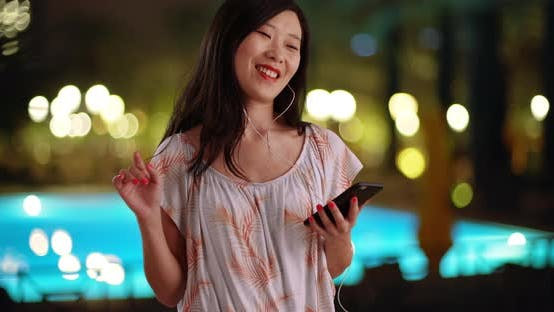 Thumbnail for Joyful millennial listening to music with smartphone at recreation center