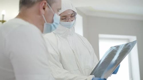 Portrait of Professional Female Doctor in Antiviral Suit Explaining Lungs Roentgen To Ill Patient