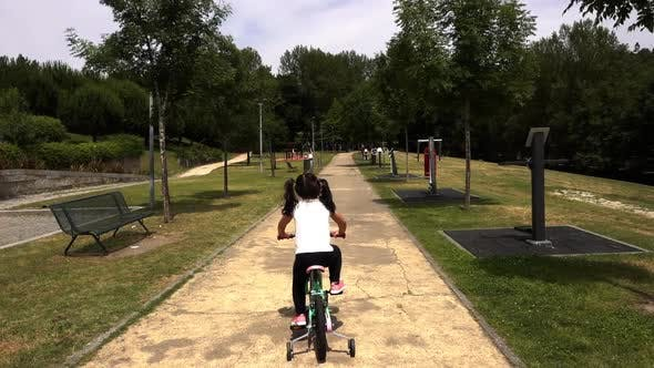 A Little Girl Riding a Bike in the Park