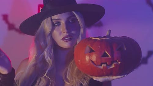 Mysterious Portrait of Young Gorgeous Enchantress Holding Halloween Pumpkin in Neon Light