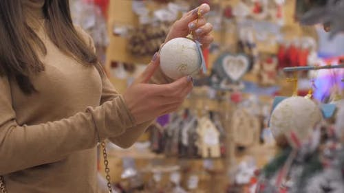 Young Woman Holds Yellow White Glittering Bauble