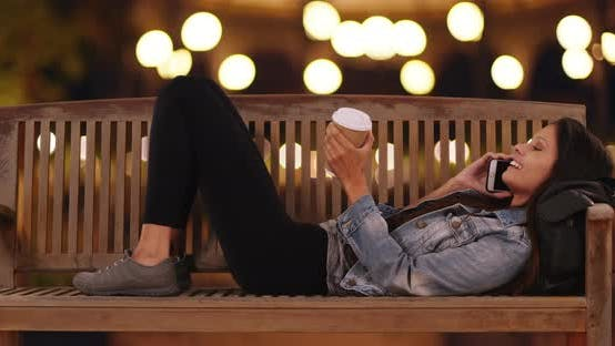 Thumbnail for Millennial female chatting on cell phone while lying on bench on city street