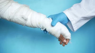 Doctor Hand in Gloves Holding Injured Painful Hand with Bandage