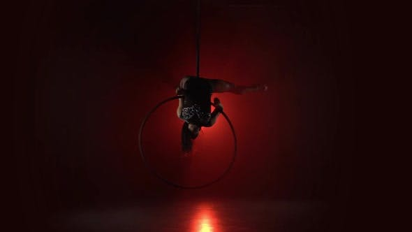 Thumbnail for Aerial Acrobat in the Ring. A Young Girl Performs the Acrobatic Elements in the Air Ring on Red