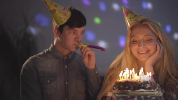 Thumbnail for Portrait of a Handsome Guy and a Girl Celebrating His Birthday Sitting at a Table with a Cake