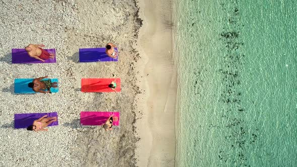Thumbnail for Aerial view of group of people doing yoga on colorful mats on sandy beach.