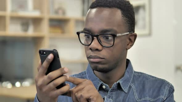 Thumbnail for Afro-American Man Browsing Smartphone