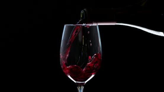 Thumbnail for Hand Pouring Wine Into the Glass. Slow Motion of Spilling Alcohol Over Black Background