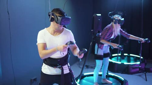 Modern Interactive Technologies Man and Woman in Glasses of Virtual Reality Playing a Arcade Game