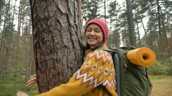 Thumbnail for Lady in Yellow Sweater and Red Hat Hugs Old Pine in Forest