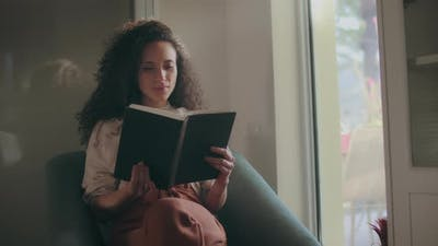 Mixed race woman reading by the window