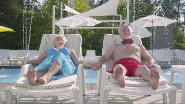 Thumbnail for Elderly Positive Couple Lying on Sunbeds Near the Pool Holding Hands and Smiling