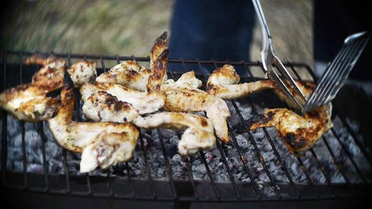 Man Cooks The Wings On The Grill