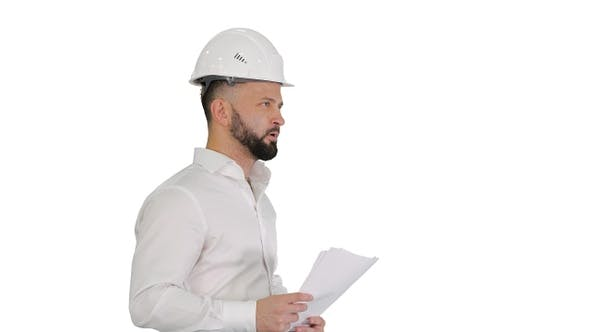 Thumbnail for Male Engineer Walking in A Hard Hat Looking at Documents
