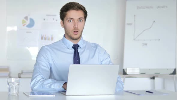 Cover Image for Surprised Young Businessman in Office Looking at Camera, Shocked