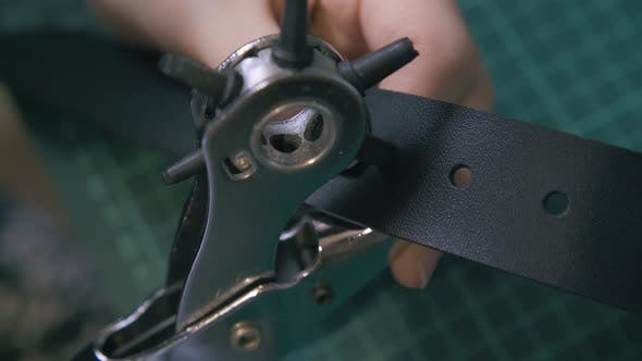 Skilled Worker Makes Holes in Leather Belt Close View