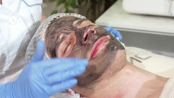 Thumbnail for Cosmetologist Preparing Face of Male Client for Carbon Facial Peeling