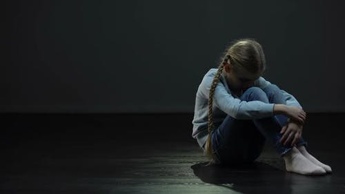 Lonely Girl Sitting in Dark Room and Looking Around