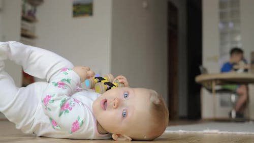 A Baby Girl in a Romper Suit Lying on the Floor