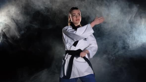 Karate kick girl in kimono practice technical shots, black by.