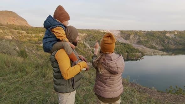 Family Looking at Map on Hike in Scenic Location