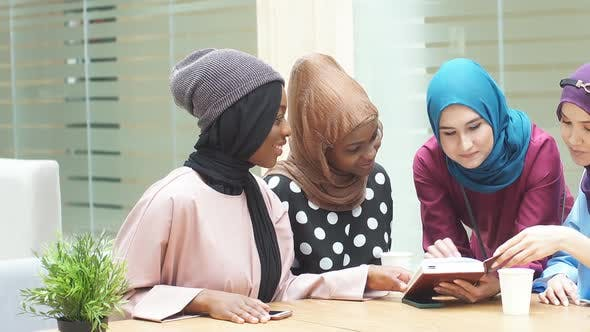 Cheerful Young Arabian Female Students Reading Book in Cafe