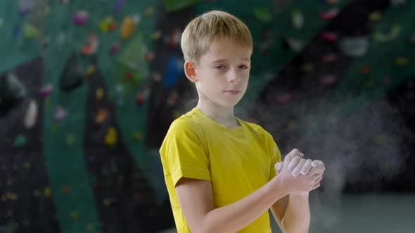 Thumbnail for Teenage Boy Clapping Hands with Chalk at Climbing Gym