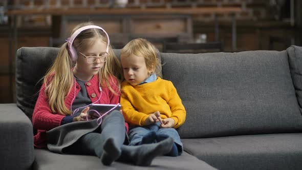 Thumbnail for Sweet Little Siblings Using Tablet Pc on Sofa
