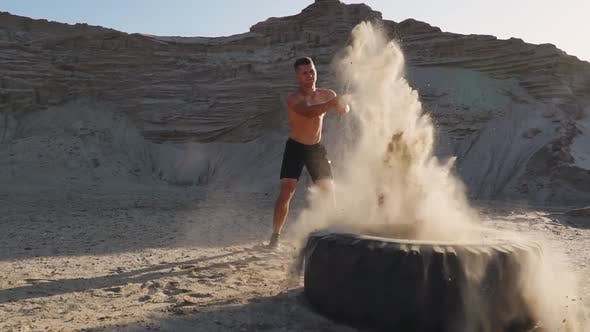 Cover Image for Muscle Athlete Strongman Man Hits a Hammer on a Huge Wheel in the Sandy Mountains in Slow Motion at
