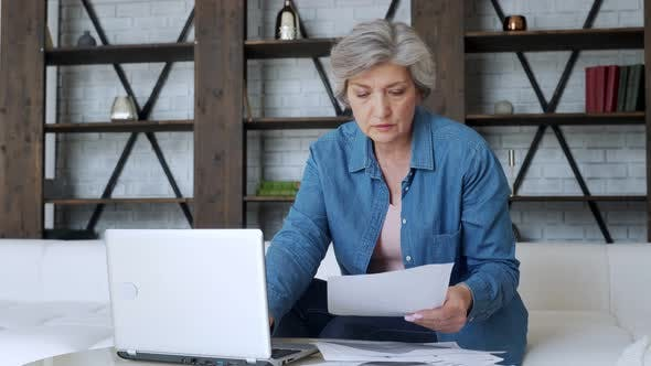 Thumbnail for Sad Elderly Retired Woman with a Depressed Look, Calculating the Family Budget, Sitting on the Sofa