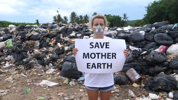 Thumbnail for Environmental Activist Standing On Waste Landfill Holding Save Earth Poster