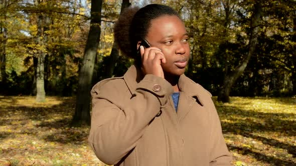 Thumbnail for Young Beautiful African Girl Stands in Woods and Phone To Someone
