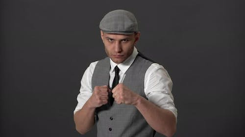 Portrait of Concentrated English Hooligan in Formal Suit and Flat Cap Clenching Fists and Ready for