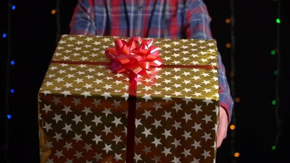 Thumbnail for Junge mit Geschenkbox auf schwarzem Hintergrund, Geschenkbox mit Band für Frohes Neues Jahr, Frohe Weihnachten