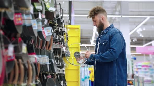 Man is Choosing Lid for Pot in Kitchen Appliances Store