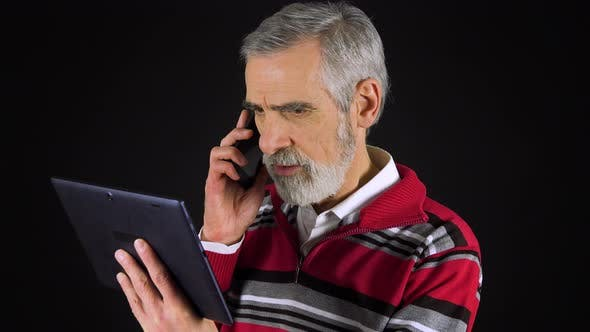 Thumbnail for An Elderly Man Holds a Tablet and Talks on a Smartphone - Black Screen Studio