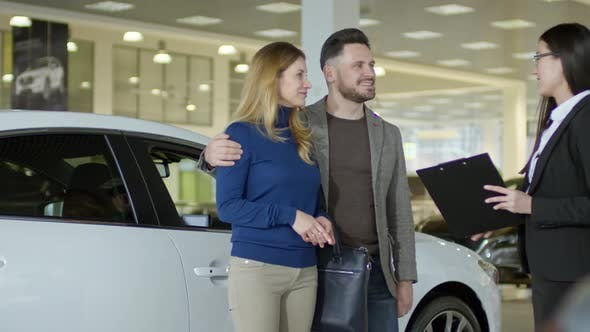 Thumbnail for Auto Saleswoman Talking with Couple at Dealership