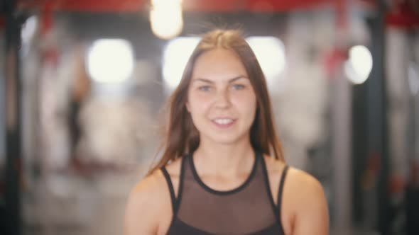 Cover Image for An Athlete Smiling Woman Pulls a Dumbbell in the Gym