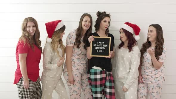 Thumbnail for Group of women in pajamas holding sign saying, Santa I have been Naughty and Nice