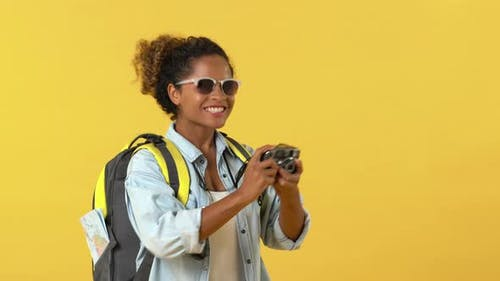 African American woman tourist backpacker taking photo