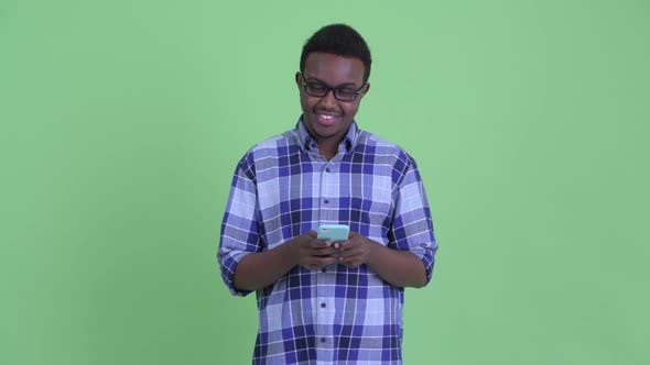 Thumbnail for Happy Young African Hipster Man Thinking While Using Phone