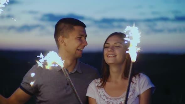 Thumbnail for Junge Leute, die Spaß auf einer Party haben, spielen mit Feuerwerk und bengalischen Lichtern