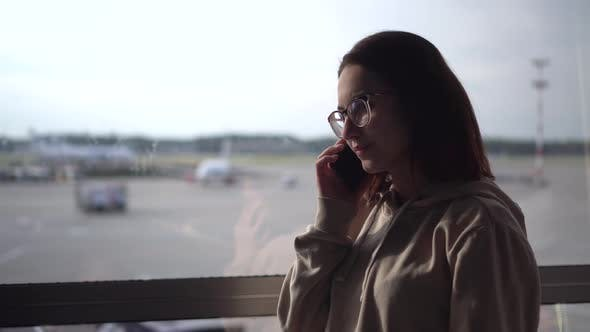 Thumbnail for A Young Woman in a Sweatshirt and Glasses Speaks on the Phone Against the Background of a Window at