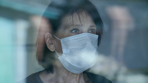 Thumbnail for Mature Woman in Medical Protective Mask Looks Out the Window